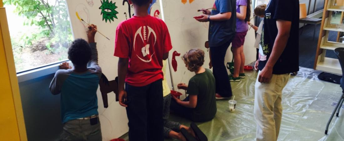 Teens are working with a Bubbler artist to paint a mural in the library.