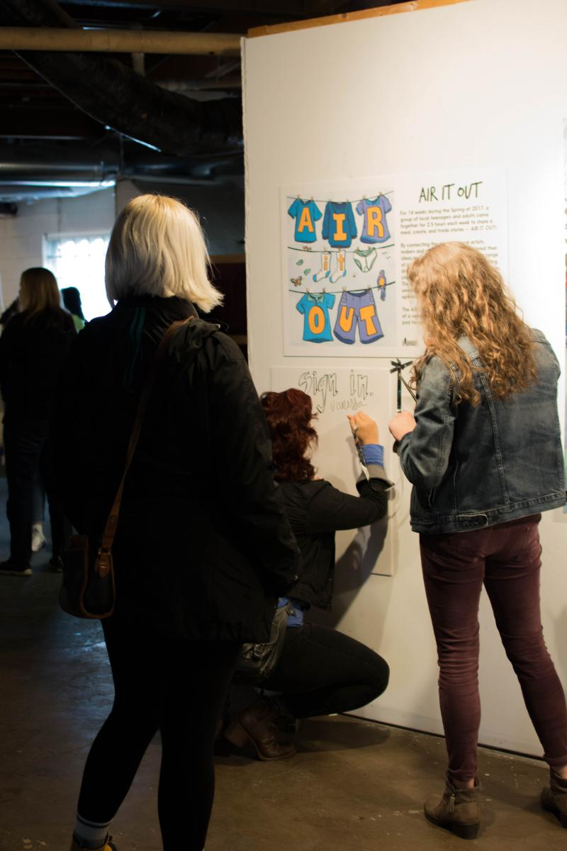 picture of people signing in at the Air It Out exhibition