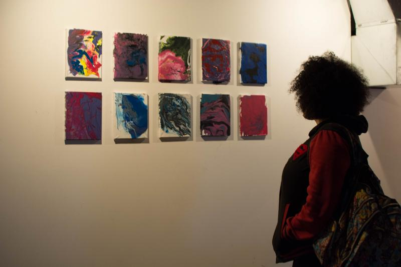 picture of teen viewing drip paintings at Air It Out teen art exhibition