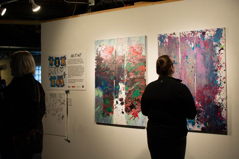 picture of someone viewing drip paintings at Air It Out teen art exhibition