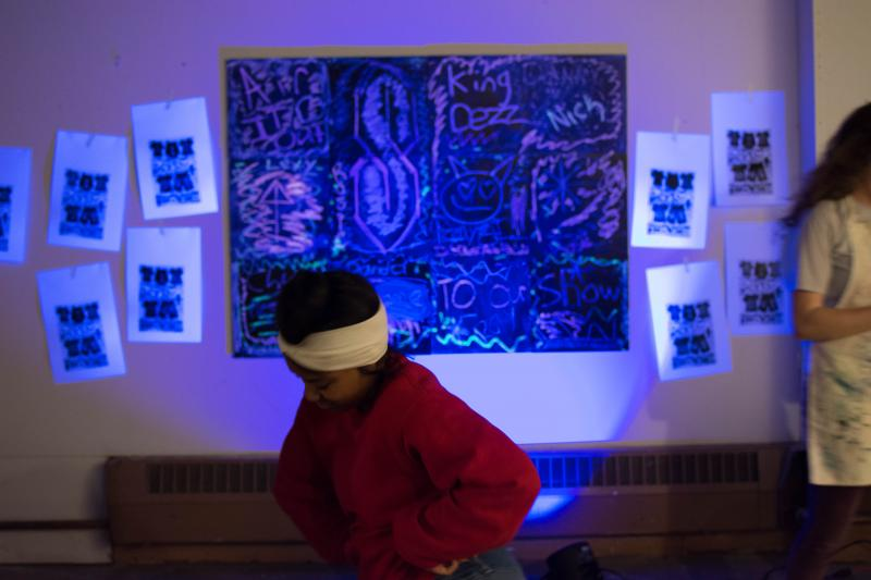 picture of teen dancing in front of black light chalk installation at Air It Out teen art exhibit