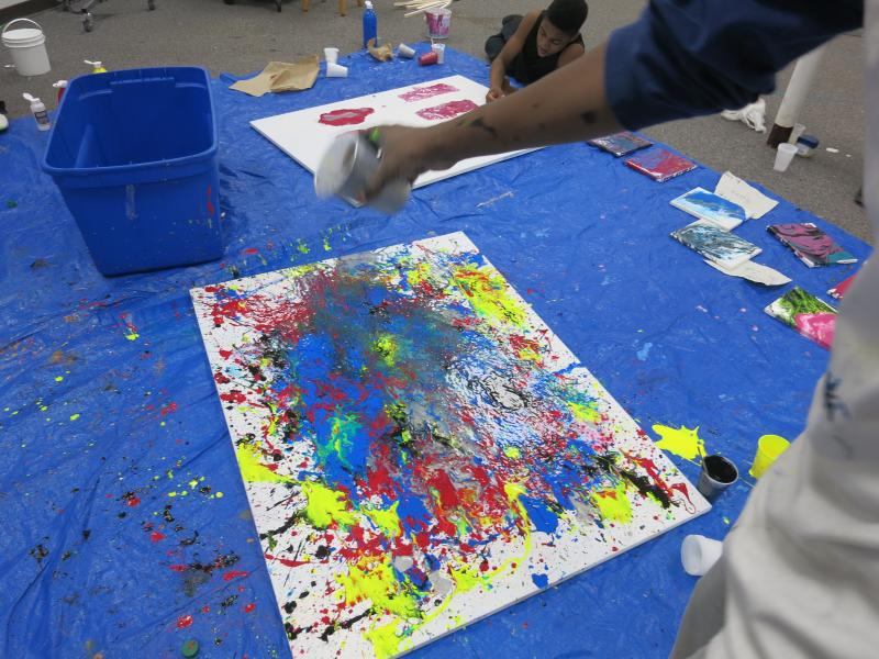 picture of teens creating drip paintings during Air It Out semester of art