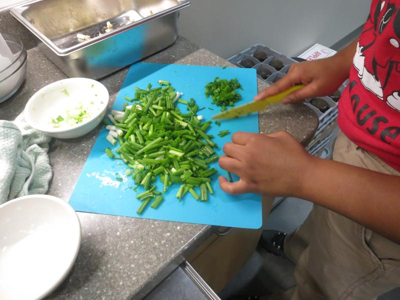Teen chopping greens