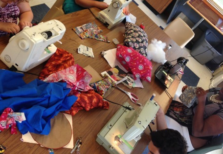 Teens use sewing machines around a large table to create pillows.