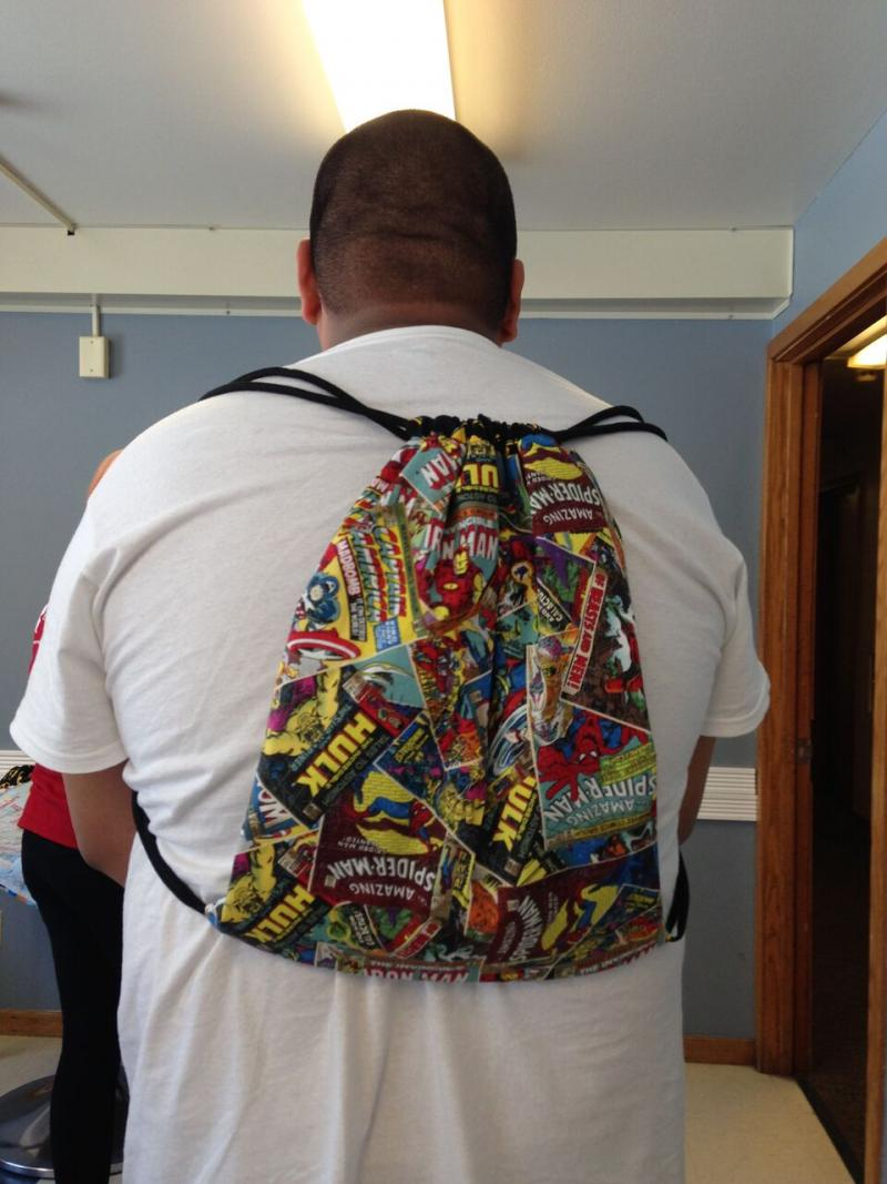 Teen wearing new backpack he made with sewing machine.