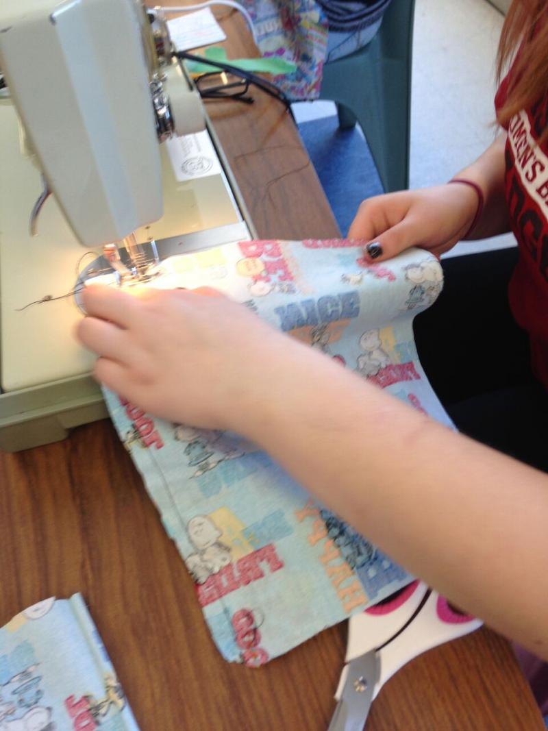 Teen sewing together fabric cutout by patterns.