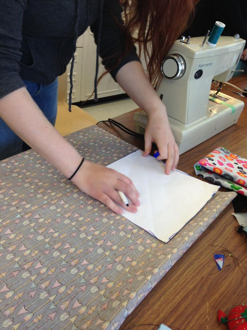Teen using pattern to cut fabric.