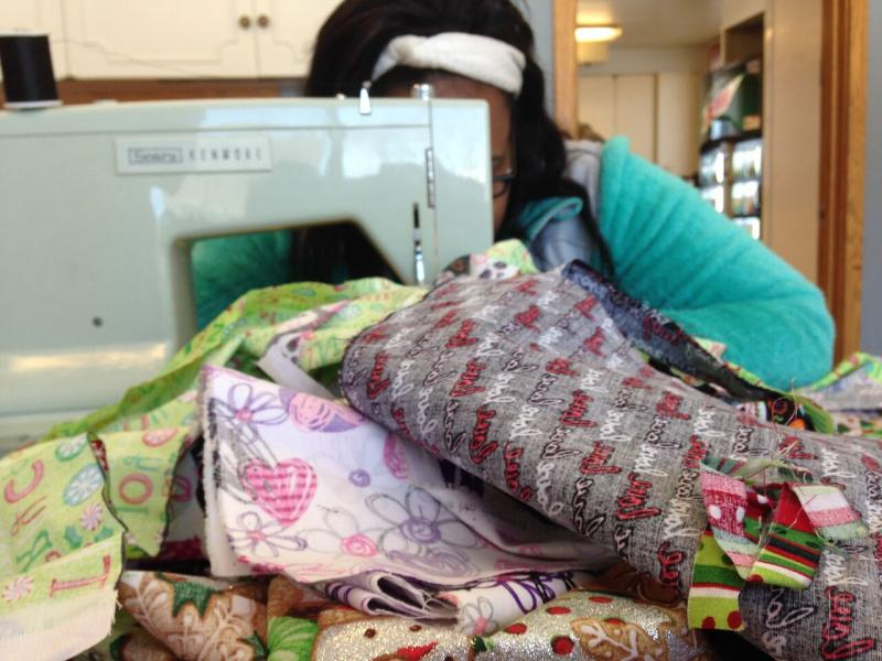 Teen using sewing machine with pile of fabric.